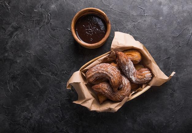 Churros dans un sac en papier avec du sucre et de la sauce au chocolat sur fond noir