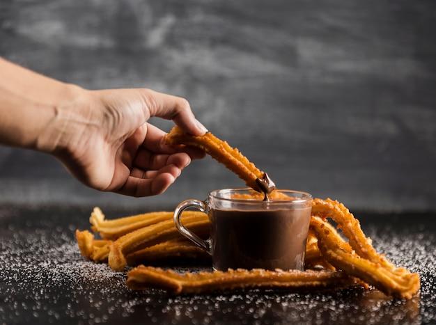 Churros délicieux avec du chocolat fondu sur la table