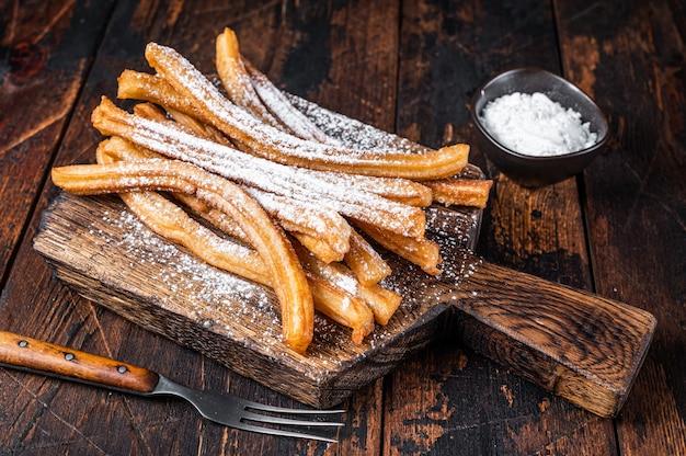 Churros de dessert espagnol avec du sucre en poudre sur un plateau en bois. bois foncé