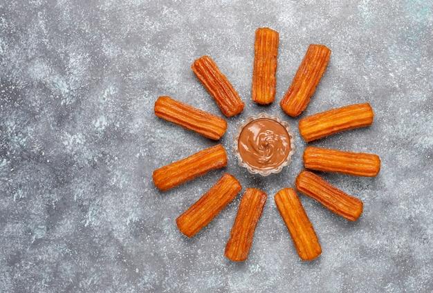Churros dessert mexicain traditionnel avec du chocolat, vue de dessus