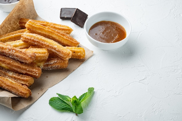 Churros dessert traditionnel espagnol avec du sucre et du chocolat, sur fond blanc avec un espace pour le texte, copyspace