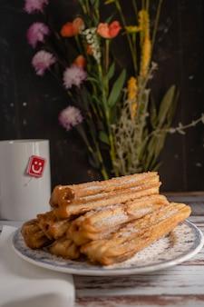 Churros hispaniques typiques remplis de dulce de leche dans une assiette vintage sur de vieilles planches. cadrage vertical, espace de copie.