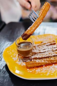 Churros piquant à la main, nappés de sucre glace et trempés dans une sauce au nutella sur une plaque jaune.