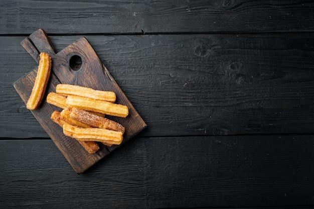 Churros saupoudrés de sucre en poudre, ensemble sur table en bois noir