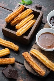 Churros typiques espagnols, pâte frite pâtisserie servi généralement avec sauce piquante au caramel au chocolat, sur le vieux fond de table en bois foncé
