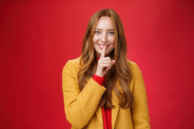 Chut, garde le secret. fille au gingembre séduisante et douce, avec des taches de rousseur, des choses mystérieuses montrant un geste de chut avec l'index sur la bouche, souriant ayant une surprise sur fond rouge.