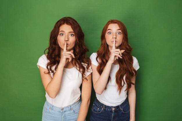 Chut! portrait de deux jeunes femmes rousses de 20 ans en tenue décontractée regardant la caméra et tenant l'index sur les lèvres, isolé sur fond vert