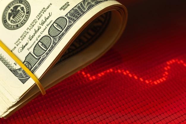 La chute de l'arrière-plan du concept de monnaie nationale avec des billets en dollars américains sur des graphiques boursiers rouges, copiez la photo de l'espace