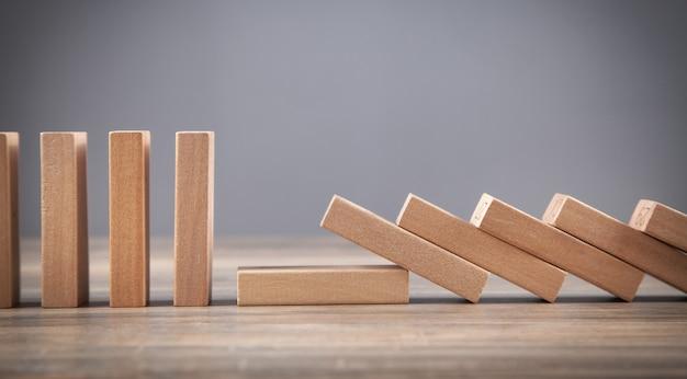 Chute de domino en bois. entreprise. crise. risque