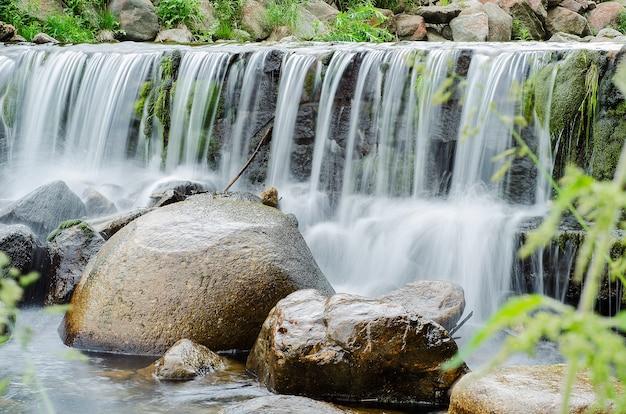 Chute d'eau sur une rivière de montagne dans la forêt