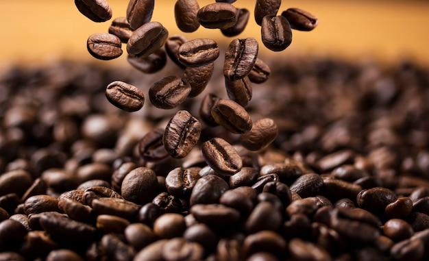 Chute de grains de café torréfiés sur une surface sombre