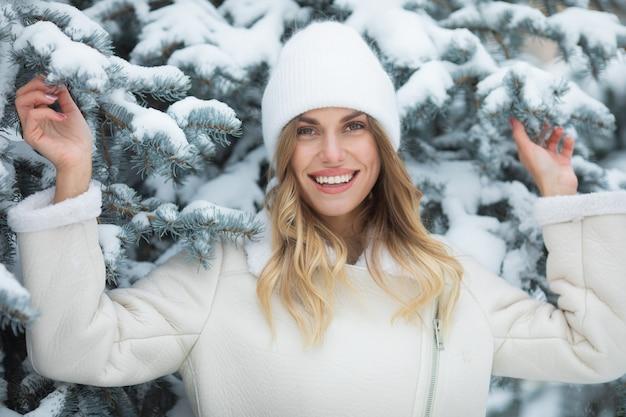 Chute de neige. la neige tombe sur la tête de la fille. femme souriante en hiver.