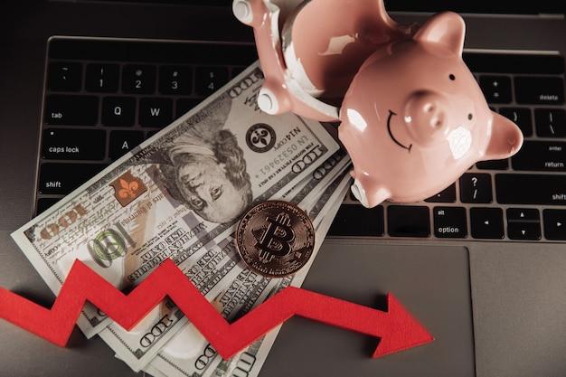 La chute de la valeur du bitcoin et du concept d'investissement bitcoin d'or tirelire cassée et flèche vers le bas sur un ordinateur portable