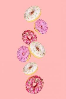 Chutes de beignets avec glaçage coloré sur fond rose tendance. lévitation de nourriture.