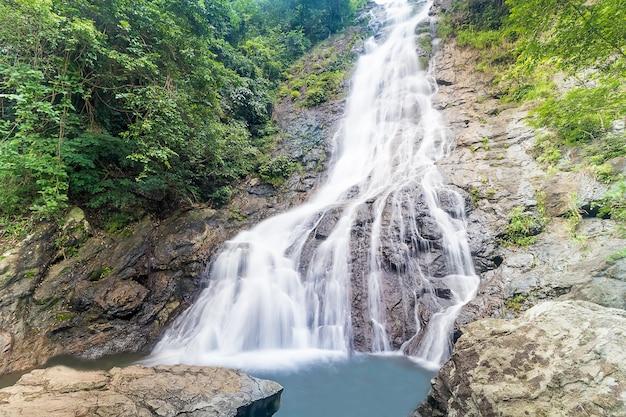 Les chutes d'eau qui coulent sur un gros morceau de roche ont beaucoup de ravins et de moss