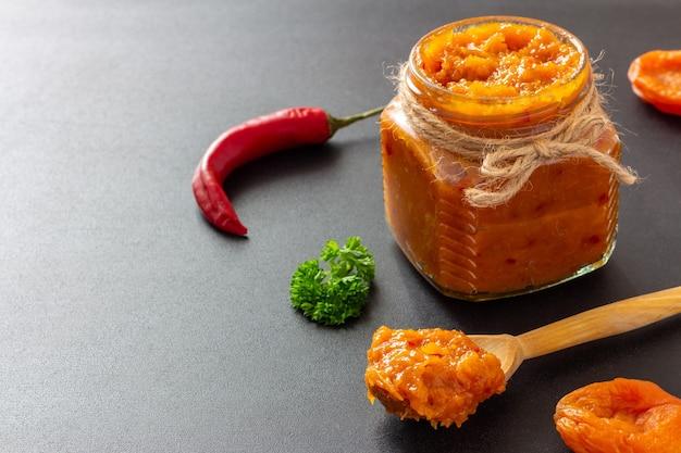 Chutney aux abricots secs épicé traditionnel avec piment fort dans un bocal en verre