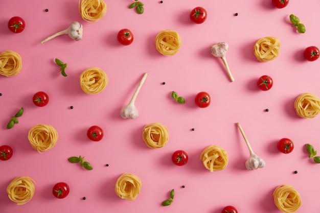Ci-dessus, des pâtes crues nourrissantes nichent l'ail, le basilic et les tomates pour préparer une savoureuse cuisine italienne. conception d'affiche de papier peint de cuisine. essayer la meilleure recette gastronomique de plat de pâtes. ingrédients pour la cuisine