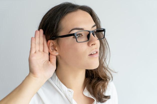 Cible fille de bureau curieuse dans des verres écoute.