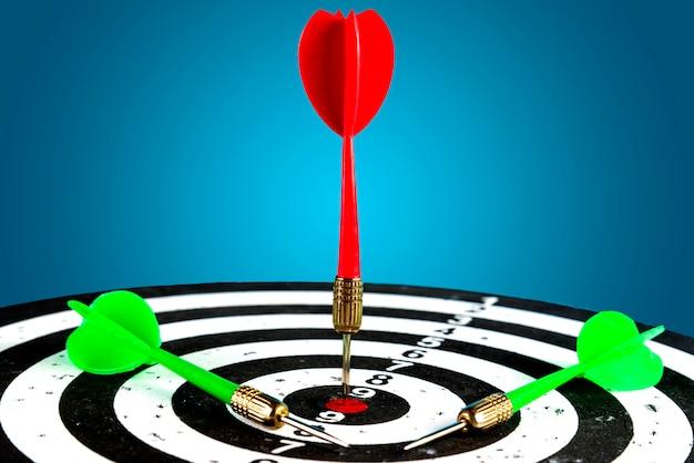 Cible avec une flèche rouge au centre et à côté sont des flèches vertes. atteindre la cible