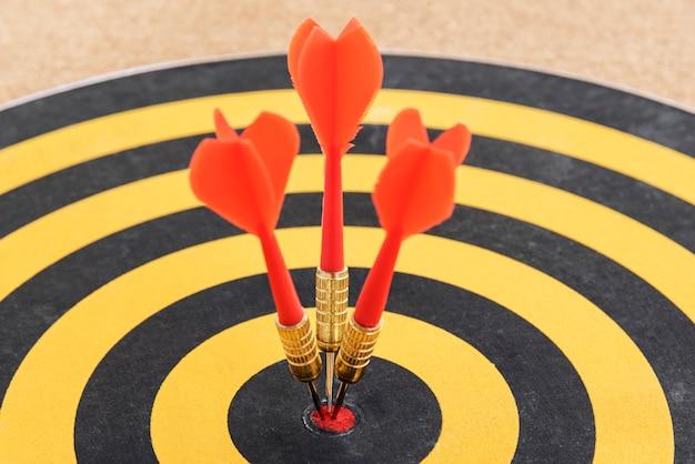 Une cible avec trois flèches de fléchettes frappant le bullseye