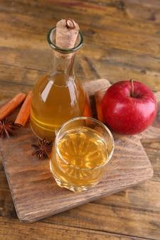 Cidre de pomme dans une bouteille en verre avec des bâtons de cannelle et des pommes fraîches sur une planche à découper, sur un mur en bois