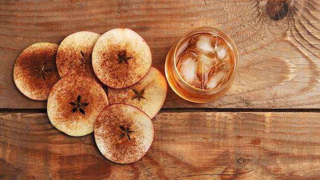 Cidre de pomme avec glace dans un verre et des tranches de pomme