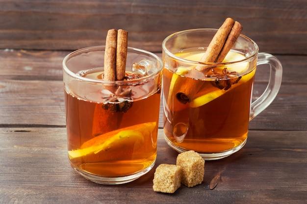 Cidre de vin chaud dans des chopes en verre avec cannelle, anis et pommes.