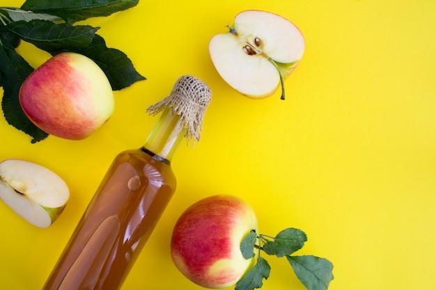 Cidre de vinaigre de pomme dans la bouteille en verre sur jaune