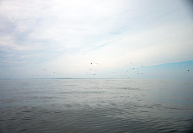 Ciel bleu avec nuages et reflet du soleil dans l'eau avec place pour votre texte. nuages anazing, brume dans le ciel