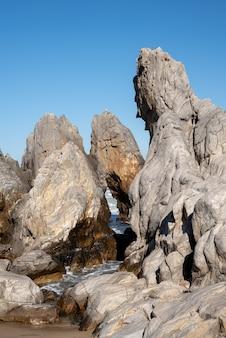 Un ciel bleu sans nuage et des roches marines de formes variées.