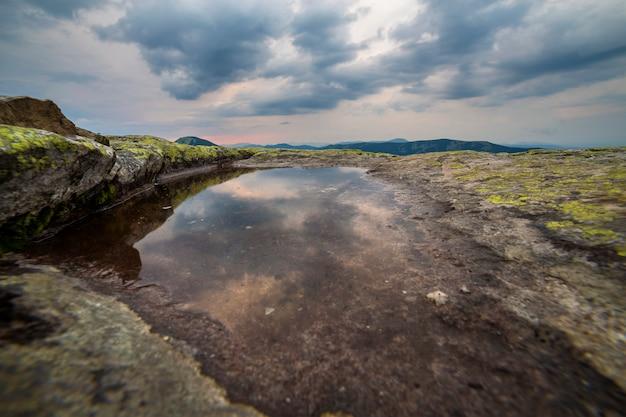 Ciel bleu se reflète dans un petit lac sur le sommet d'une montagne rocheuse sur la chaîne de montagnes bleue à l'aube.