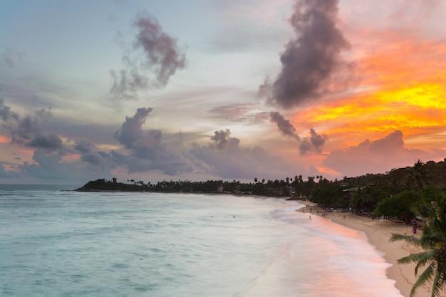 Ciel coloré au coucher du soleil sur une plage tropicale déserte