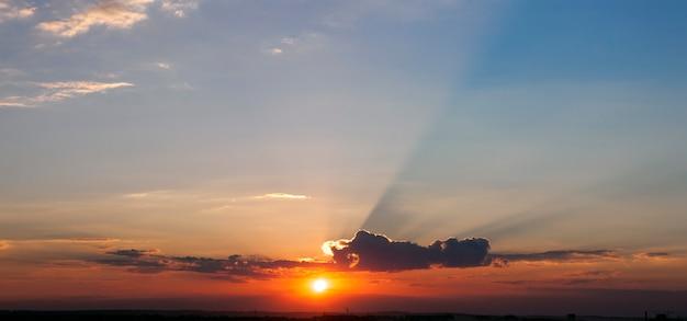 Ciel coucher de soleil spectaculaire avec des beames de lumière à travers un panorama de nuages