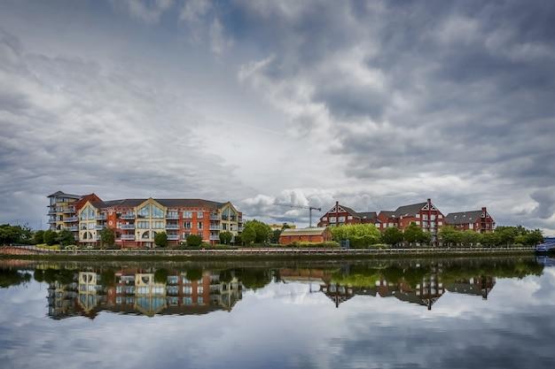 Ciel dramatique sur l'architecture moderne le long de la rivière lagan à belfast, en irlande du nord