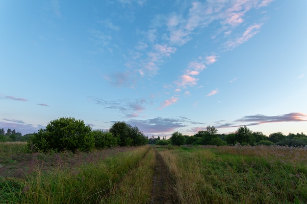 Ciel du soir avec demi-lune et route rurale sur la campagne.