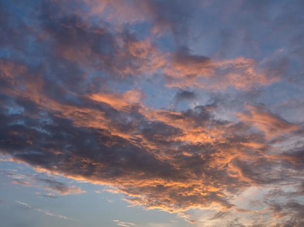 Ciel du soir avec des nuages bleus, blancs et orange.