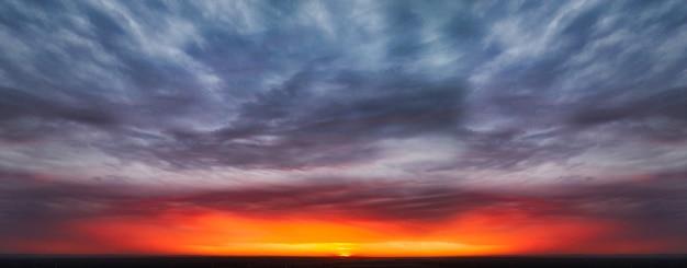 Le ciel épique symétrique avec un éclair lumineux du soleil parmi les nuages noirs au coucher du soleil
