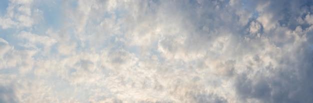 Le ciel est couvert de petits nuages, éclairés par la lumière du soleil du soir. panorama