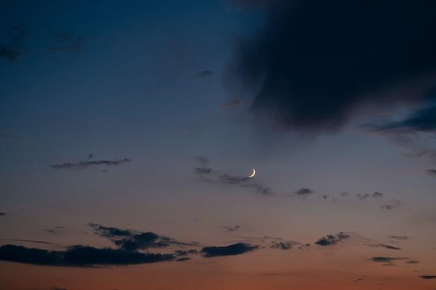 Ciel d'été de nuit avec ciel coucher de soleil et jeune lune