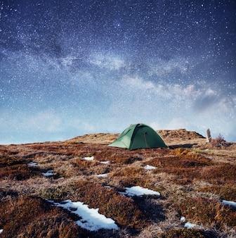Le ciel étoilé au-dessus de la tente dans les montagnes.