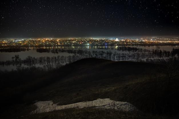 Ciel étoilé au-dessus de la ville et de la rivière pendant les crues printanières
