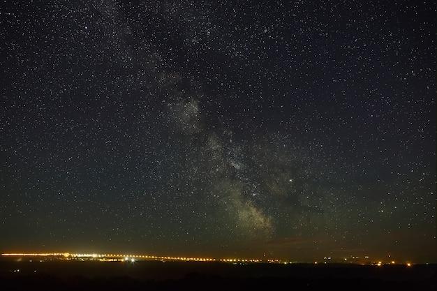 Ciel étoilé avec la voie lactée au-dessus de la ville avec éclairage.
