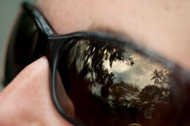 Ciel et forêt se reflètent dans des lentilles de lunettes de soleil noires
