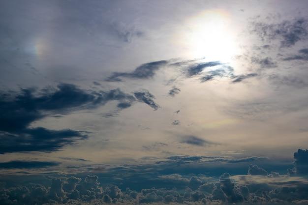 Ciel gris foncé avec nuages et soleil dans le coin supérieur droit.
