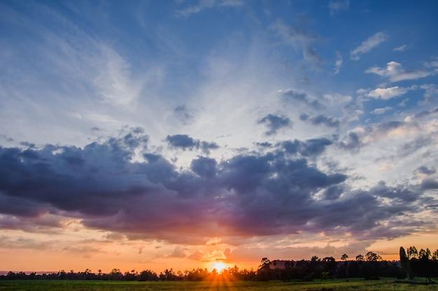 Ciel et mer brûlants au coucher du soleil avec des couleurs vibrantes et des formations nuageuses impressionnantes après la pluie et l'orage.