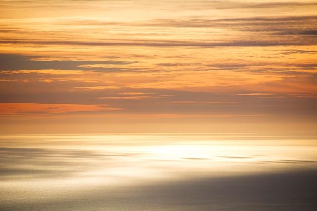 Le ciel et la mer se mêlent en orange au coucher du soleil