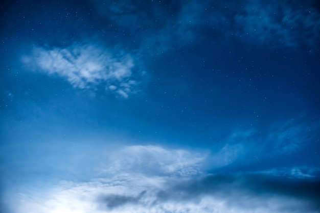 Ciel nocturne bleu foncé avec de nombreuses étoiles et lune brillante montante. fond de la voie lactée