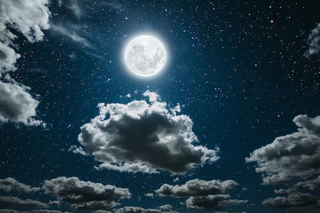 Ciel nocturne avec étoiles et lune et nuages.