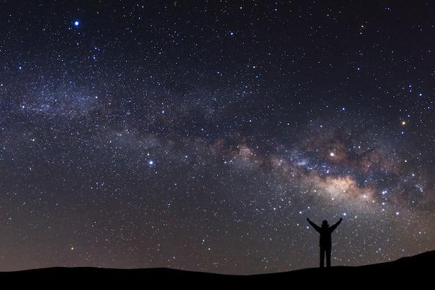 Ciel nocturne avec des étoiles et la silhouette d'un homme sportif debout avec les bras levés