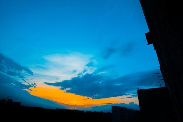 Ciel nuageux bleu atmosphérique derrière les silhouettes des bâtiments de la ville. cobalt et orange du lever du soleil avec des nuages denses et une lumière ensoleillée jaune vif pour l'espace de copie. ciel cyan au-dessus des nuages.
